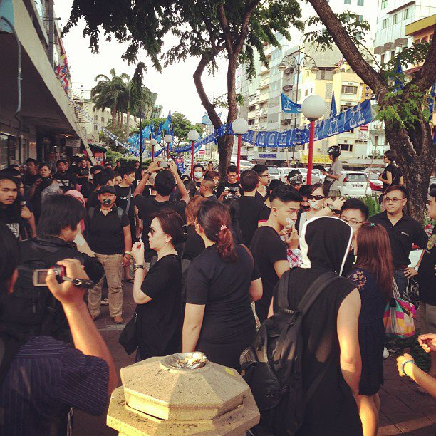 Groups of people wearing black and taping their mouth while walking silently and peacefully from Suria Sabah to UMNO building. The walk ended with a police raid.